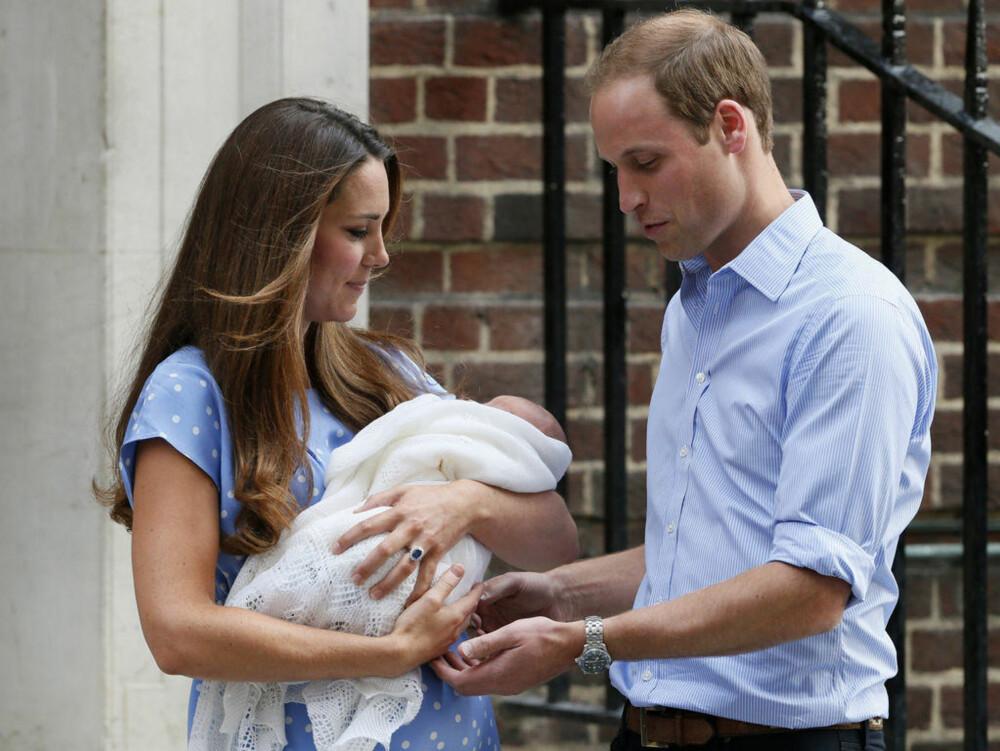 Stolte foreldre med lille George i armene.