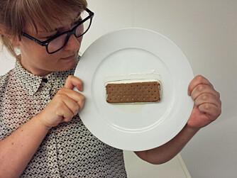 HENGER FAST: Journalist Annika Bohnenblust holder oppe en Sandwich fra Diplom-Is som har ligget på tallerkenen i 24 timer - nesten uten å miste fasongen. Fasongen endres heller ikke når tallerkenen står på høykant.