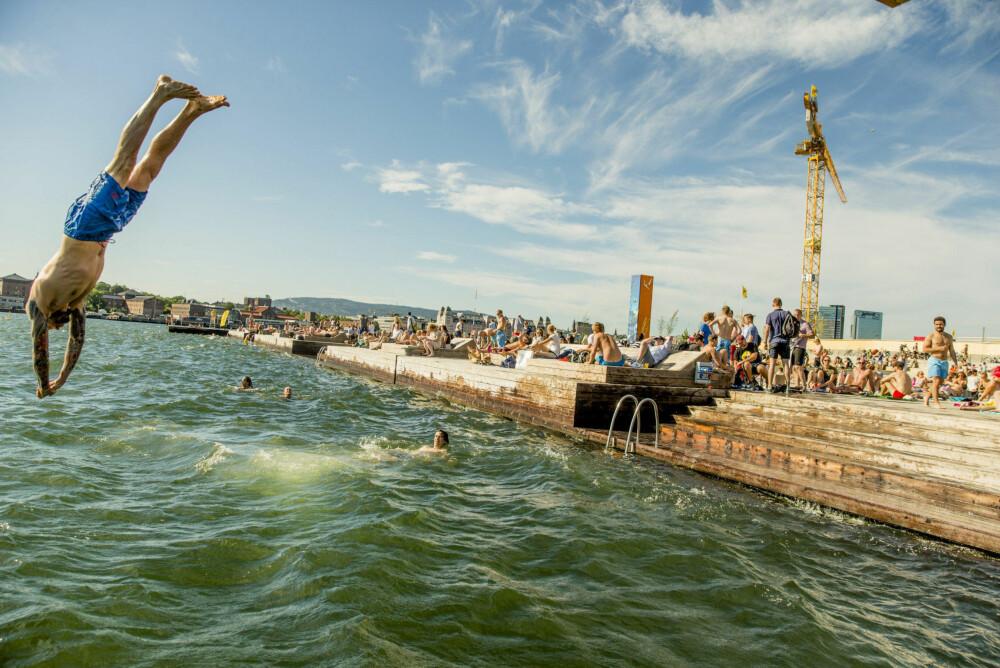 Folk nyter sol, sommer og bading på Sørenga i Oslo.