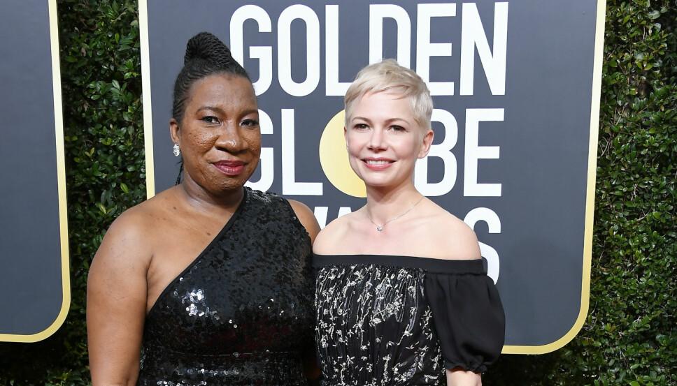 KOM SAMMEN: Tarana Burke kom sammen med Michelle Williams under Golden Globe-utdelingen. Alle de kvinnelige stjernene, og de fleste mannlige, kom kledd i svart for å vise sin støtte til ofre for seksuell trakassering.