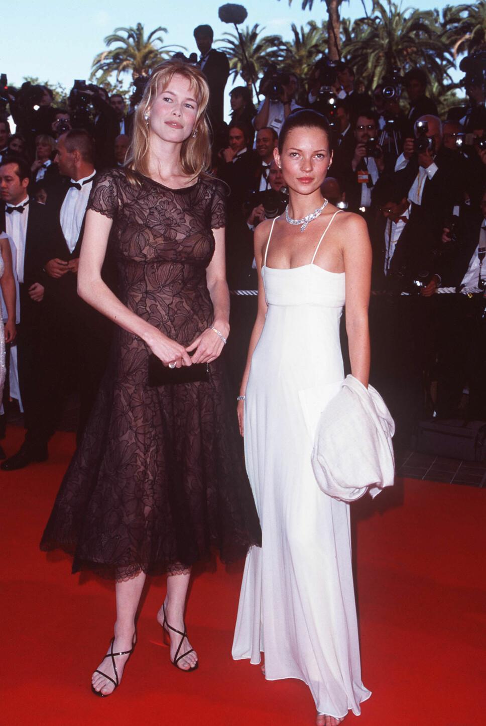ENKELT: Kate Moss i en enkel, hvit silkekjole med spaghettistropper under filmfestivalen i Cannes i 1998. Her poserer hun på den røde løperen med modellkollega Claudia Schiffer.