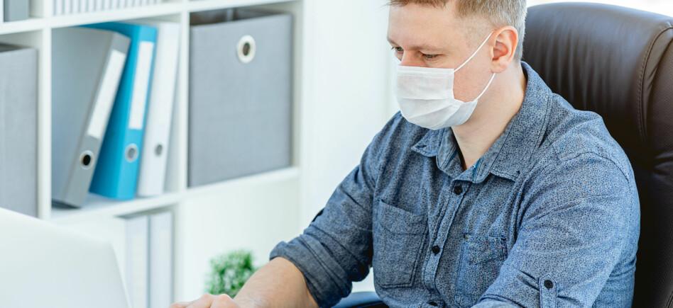 Man wearing medical face mask working on laptop